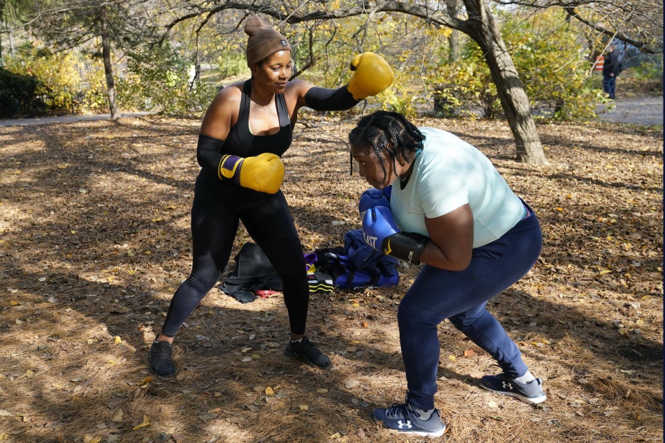 Sharon Antoine, right, ducks a swing from boxing partner Erica Plante, as they workout in Prospect Park, Sunday, Nov. 15, 2020, in the Brooklyn borough of New York. Plante said Fitness 4040, the East New York gym where the pair used to workout, closed during the pandemic, so the women moved outdoors to Prospect Park. (AP Photo/Kathy Willens)