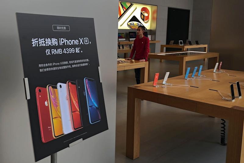 A trade-in for iPhone XR promotion board is displayed as an Apple employee waits for customer at its retail store in Beijing, Thursday, Jan. 3, 2019. Apple Inc.'s $1,000 iPhone is a tough sell to Chinese consumers who are jittery over an economic slump and a trade war with Washington. The tech giant became the latest global company to collide with Chinese consumer anxiety when CEO Tim Cook said iPhone demand is waning, due mostly to China. Weak consumer demand in the world's second-largest economy is a blow to industries from autos to designer clothing that are counting on China to drive revenue growth. (AP Photo/Andy Wong)