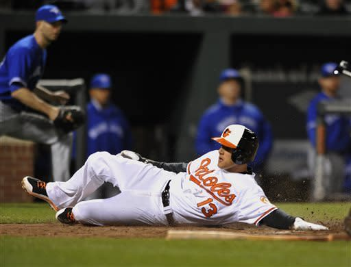 Baltimore Oriole's Manny Machado crosses the plate to score on a sacrifice fly by Chris Davis against the Toronto Blue Jays in the sixth inning of a baseball game Monday, April 22, 2013 in Baltimore. (AP Photo/Gail Burton)