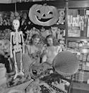 <p>Halloween stores in the mid-1900s and Halloween stores now seem to have one thing in common: an endless supply of decorations. These two women are examining a paper skeleton in a hallway full of pumpkins, owls, and creepy dolls. <br></p>