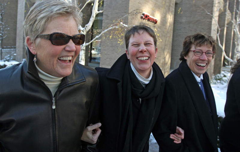 FILE - In this Dec. 4, 2013 file photo, plaintiffs Laurie Wood, left, and her partner, Kody Partridge, center, walk with their attorney Peggy Tomsic after leaving the Frank E. Moss United States Courthouse in Salt Lake City. A federal judge struck down Utah's same-sex marriage ban Friday, Dec. 20, 2013, in a decision that brings a nationwide shift toward allowing gay marriage to a conservative state where the Mormon church has long been against it. (AP Photo/Rick Bowmer, File)