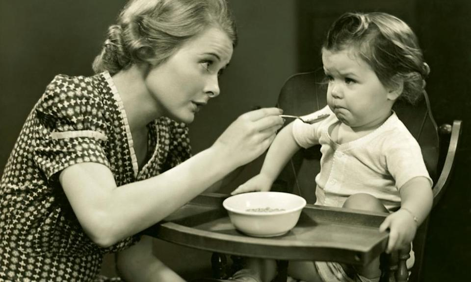1950s  Woman trying to feed baby.