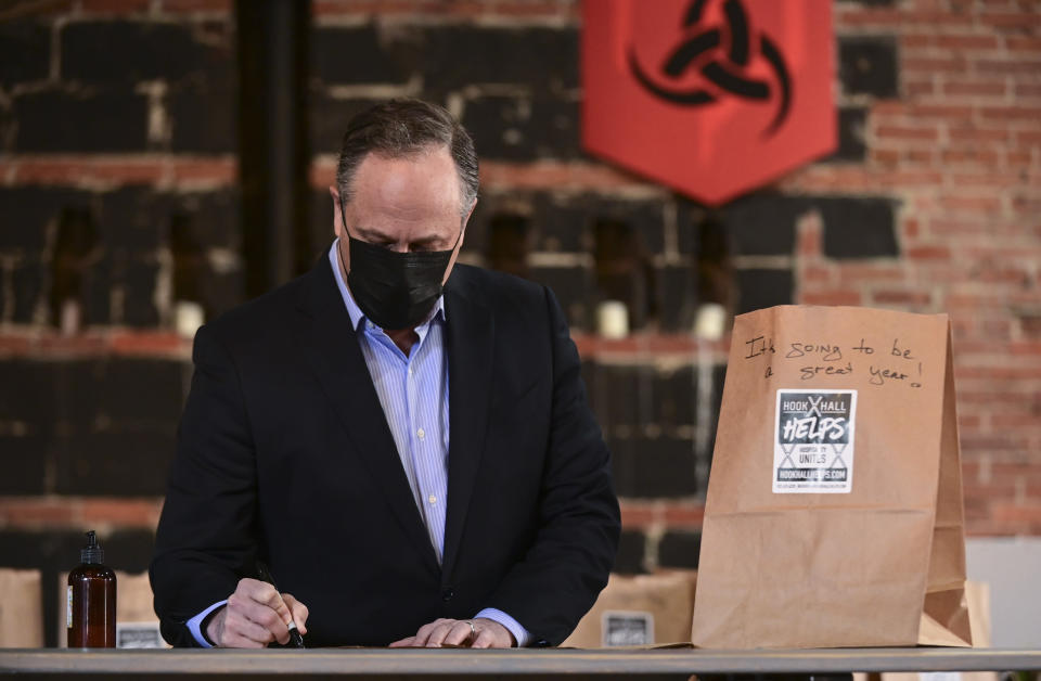 """Doug Emhoff, husband of Vice President Kamala Harris, writes messages on relief packages as they tour """"Hook Hall Helps"""" a COVID-19 relief effort that organizes and distributes prepared meals and care kits to local hospitality workers whose jobs have been impacted by pandemic-related shutdowns and restrictions, during a visit to the organization in Washington, on Monday, March 8, 2021. (Erin Scott/Pool via AP)"""
