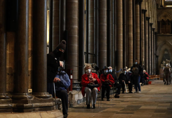 People sit down and relax after receiving their Pfizer-BioNTech vaccination at Salisbury Cathedral in Salisbury, England, Wednesday, Jan. 20, 2021. Salisbury Cathedral opened its doors for the second time as a venue for the Sarum South Primary Care Network COVID-19 Local Vaccination Service. (AP Photo/Frank Augstein)