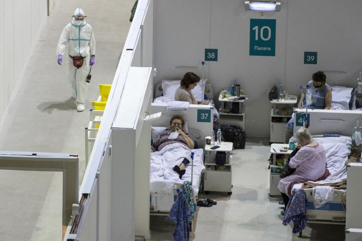 A medical worker walks next to patients in the treatment hall of a temporary hospital for coronavirus patients in the Krylatskoye Ice Palace in Moscow, Russia, Wednesday, Nov. 18, 2020. Russia's health care system has been under severe strain in recent weeks, as a resurgence of the coronavirus pandemic has swept the country. (AP Photo/Pavel Golovkin)
