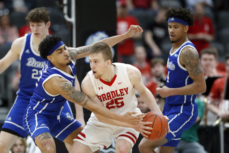 Bradley's Nate Kennell (25) keeps the ball away from Drake's Roman Penn, left, as Drake's Anthony Murphy, right, watches during the second half of an NCAA college basketball game in the semifinal round of the Missouri Valley Conference men's tournament Saturday, March 7, 2020, in St. Louis. (AP Photo/Jeff Roberson)