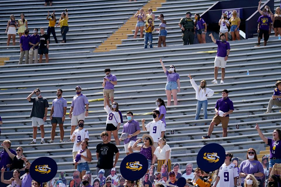 A limited number of fans in the student section, seated according to COVID-19 restrictions requiring social distancing and masks, watch a college football game between LSU and Mississippi State in Baton Rouge, Louisiana.