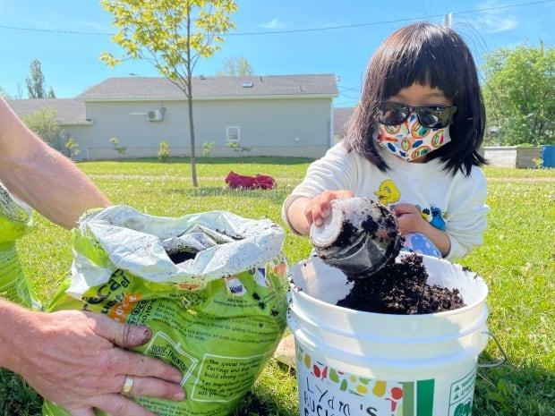 Though the workshop was for kids a few years older, four-year-old Lydia Yip got her hands dirty. (Tony Davis/CBC - image credit)