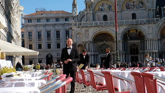 Waiters at an empty restaurant in St Mark's Square. (Reuters/Manuel Silvestri)