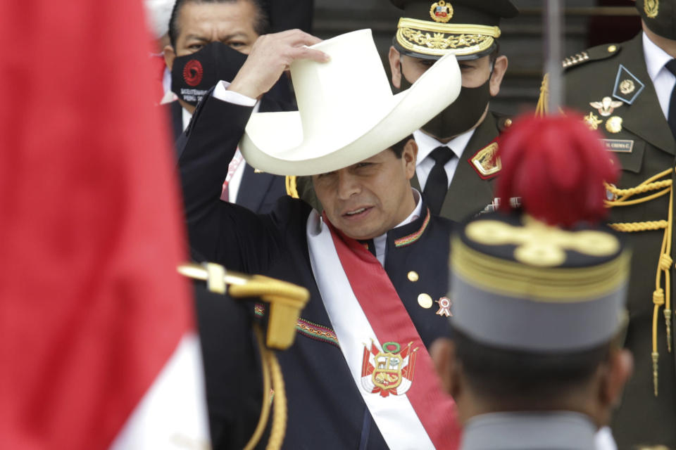 """Peru's newly sworn-in President Pedro Castillo puts his hat back on after taking it off momentarily to acknowledge the Peruvian flag held by soldiers outside Congress on his inauguration day in Lima, Peru, Wednesday, July 28, 2021. The rural teacher popularized the phrase """"No more poor in a rich country,"""" and stunned millions of Peruvians and observers by advancing to the runoff. (AP Photo/Francisco Rodriguez)"""