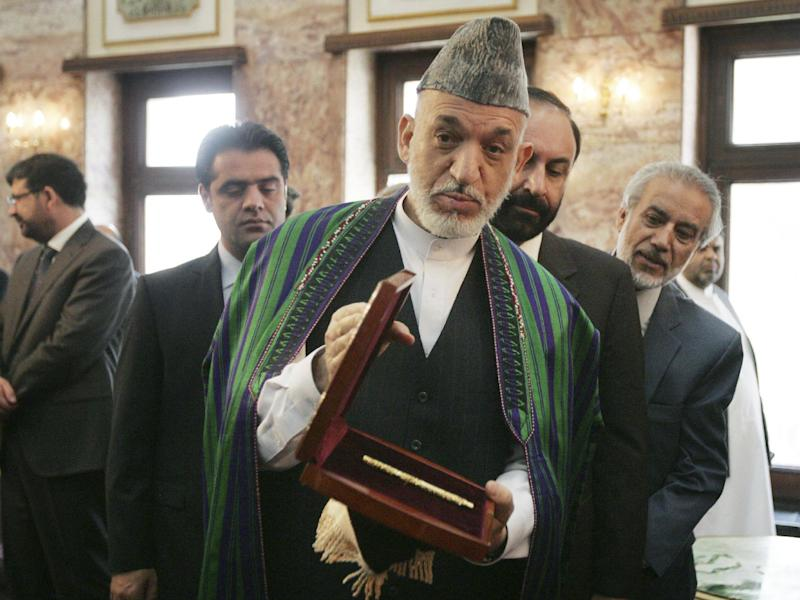 Afghan President Hamid Karzai displays a case containing a pen that belonged to former Afghanistan King Shah Amanullah Khan, who ruled the country from 1919 to 1929, during a ceremony at the presidential palace in Kabul, Afghanistan, Monday, Aug. 27, 2012. The pen will be transferred to the Afghan National Museum. (AP Photo/Ahmad Massoud / Xinhua, Pool)