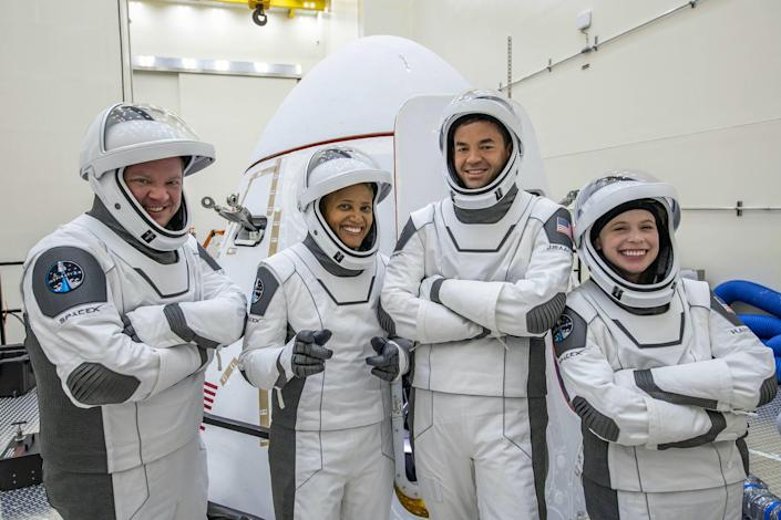 inspiration4 crew members pose in white grey spacex spacesuits in front of crew dragon spaceship
