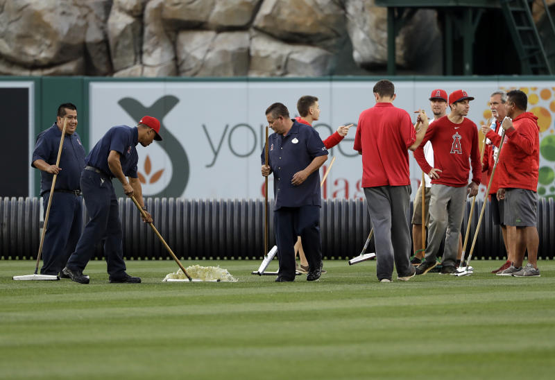 Members of the grounds crew try to clear water from the outfield before a baseball game between the Los Angeles Angels and the Minnesota Twins on Wednesday, May 22, 2019, in Anaheim, Calif. The game was rained out. (AP Photo/Marcio Jose Sanchez)