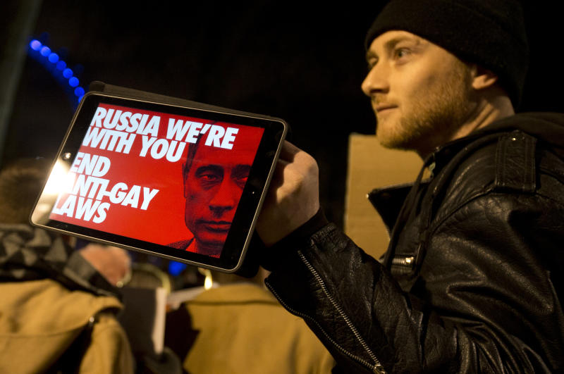 A Lesbian and Gay Rights activist holds up a tablet with a picture of a placard, during a demonstration aimed to coincide with the upcoming Winter Olympics in Sochi, Russia, against laws aimed at stifling Gay Rights in Russia, opposite Downing Street in London, Wednesday, Feb. 5, 2014. In London, about 150 people rallying outside Prime Minister David Cameron's office in London urged McDonald's and the IOC's other sponsors to speak out. The activists there said they plan to deliver a petition signed by more than 100,000 people to a nearby McDonald's restaurant. (AP Photo/Alastair Grant)