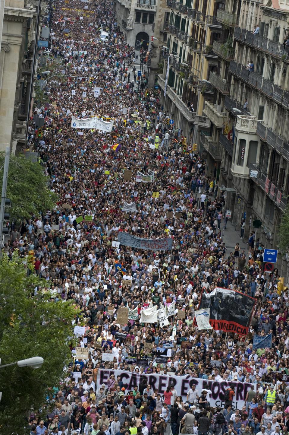 """Thousand of 'indignants' hold banners and shout slogans against the Euro zone leaders's agreed 'Pact For The Euro' on June 19, 2011 in Barcelona, Spain. Thousands of Spaniards joined marches across Spain to protest against how the country's economic crisis is being handled and the so-called """"Euro Pact"""", aimed at increasing the bloc's competitiveness and economic stability. (Photo by David Ramos/Getty Images)"""