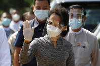 Myanmar leader Aung San Suu Kyi wearing protective face mask and shield waves to supporters as she leaves a demonstration of the voting for upcoming Nov. 8 general election, Tuesday, Oct. 20, 2020, in Naypyitaw, Myanmar. (AP Photo/Aung Shine Oo)