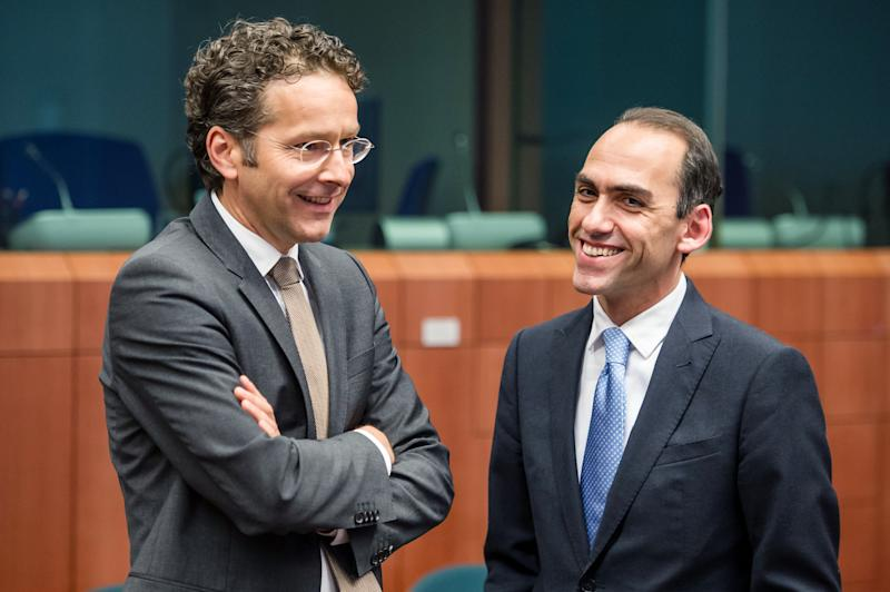 Cyprus' Finance Minister Haris Georgiades, right, smiles as he talks with Eurogroup President Jeroen Dijsselbloem at the start of an Eurogroup meeting at the EU Council in Brussels on Monday, May 13, 2013. (AP Photo/Geert Vanden Wijngaert)