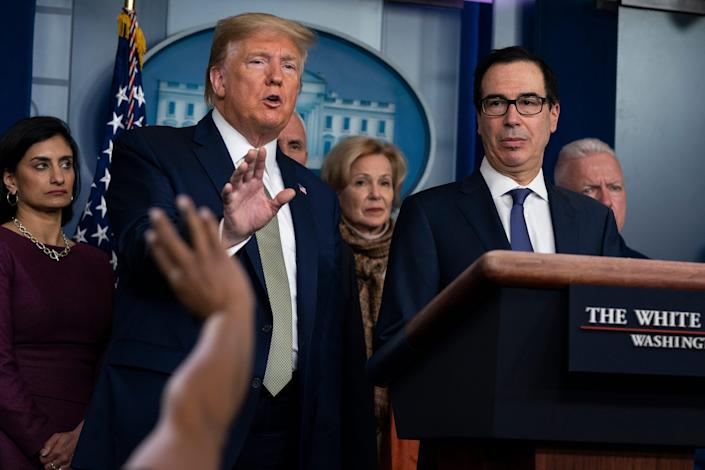 Treasury Secretary Steven Mnuchin, right, listens as President Donald Trump speaks during a press briefing with the coronavirus task force, at the White House, Tuesday, March 17, 2020.