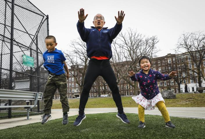 A father, son and young daughter jump while exercising outdoors together