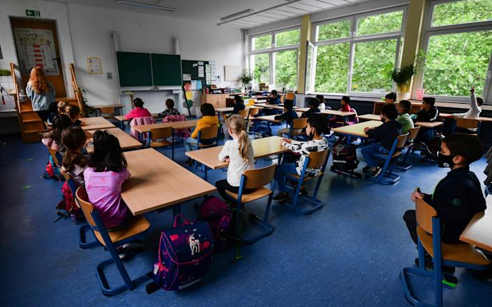 Students sit in a classroom of the Petri primary school in Dortmund, western Germany, on June 15, 2020 amid the novel coronavirus COVID-19 pandemic. - From June 15, 2020, all children of primary school age in the western federal state of North Rhine-Westphalia will once again be attending regular daily classes until the summer holidays. The distance rules and compulsory mouthguards are no longer applicable. (Photo by Ina FASSBENDER / AFP) (Photo by INA FASSBENDER/AFP via Getty Images) - INA FASSBENDER/AFP