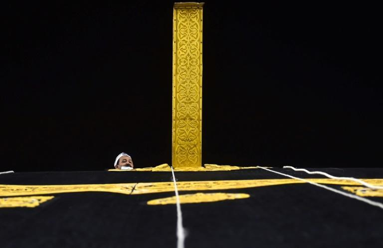 A Saudi workman adjusts the new kiswa, the gold-embroidered black cloth covering the Kaaba, that is changed during each year's hajj