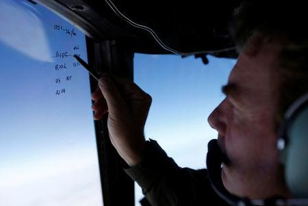Squadron leader Brett McKenzie marks the name of another search aircraft on the windshield of a Royal New Zealand Air Force P-3K2 Orion aircraft searching for missing Malaysian Airlines flight MH370 over the southern Indian Ocean March 22, 2014.   REUTERS/Jason Reed/File Photo