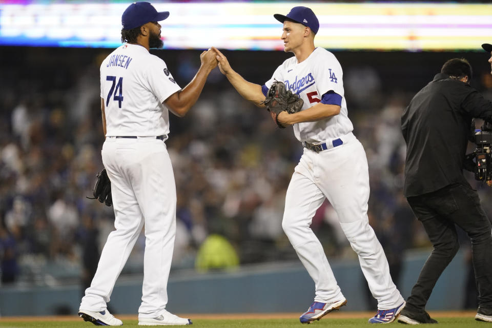 Los Angeles Dodgers relief pitcher Kenley Jansen (74) and shortstop Corey Seager (5) celebrate an 8-6 win over the Milwaukee Brewers after their a baseball game Friday, Sept. 1, 2021, in Los Angeles. (AP Photo/Ashley Landis)