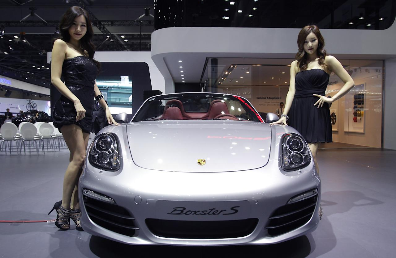 GOYANG, SOUTH KOREA - MARCH 28:  Models pose next to a Porsche Boxster S at the Seoul Motor Show 2013 on March 28, 2013 in Goyang, South Korea. The Seoul Motor Show 2013 will be held in March 29-April 7, featuring state-of-the-art technologies and concept cars from global automakers. The show is its ninth since the first one was held in 1995. About 384 companies from 14 countries, including auto parts manufacturers and tire makers, will set up booths to showcase trends in their respective industries, and to promote their latest products during the show.  (Photo by Chung Sung-Jun/Getty Images)