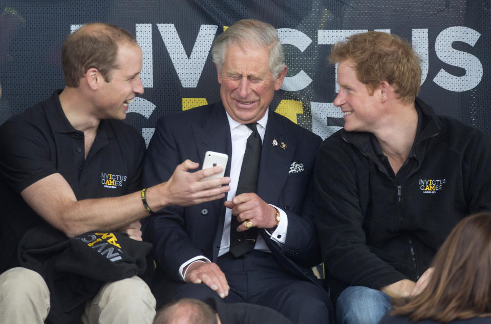 Britain's Princes William (L), Charles (C) and Harry look at a mobile phone during the Invictus Games in the Lee Valley Athletics Centre in north London September 11, 2014. The Invictus Games which will run from September 10-14, is an international sporting event for wounded servicemen and women from 13 countries.   REUTERS/Neil Hall (BRITAIN - tags: SPORT - Tags: ENTERTAINMENT MILITARY SOCIETY ROYALS SPORT)
