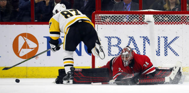 Carolina Hurricanes goaltender Petr Mrazek (34) blocks the shot of Pittsburgh Penguins' Sidney Crosby (87) during the shoot out of an NHL hockey game, Tuesday, March 19, 2019, in Raleigh, N.C. Hurricanes won 3-2 by shoot out. (AP Photo/Karl B DeBlaker)