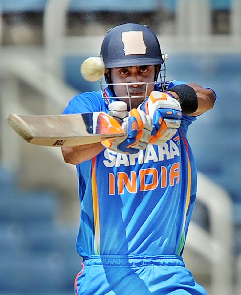Indian cricketer Manoj Tiwary hits a boundary off West Indies cricket team captain Darren Sammy during the fifth One Day International match between West Indies and India at the   Sabina Park Stadium in Kingston on June 16, 2011.