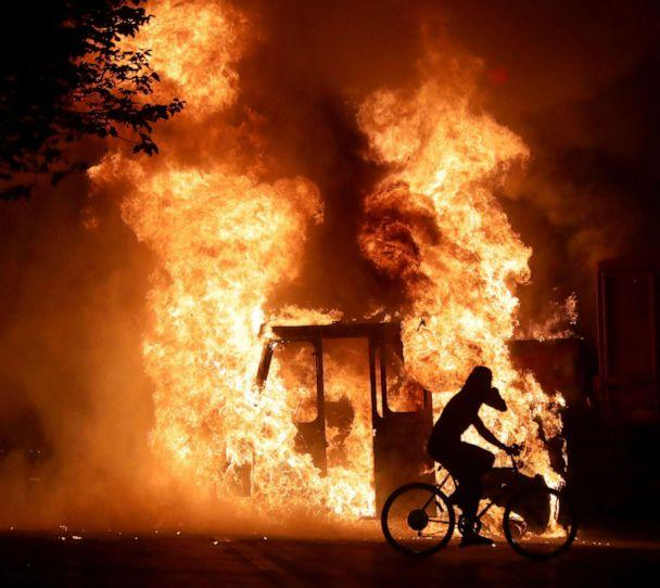 PHOTO: A man on a bike rides past a city truck on fire outside the Kenosha County Courthouse in Kenosha, Wis., Aug 23, 2020, during protests following the police shooting of Jacob Blake. (Mike de Sisti/Milwaukee Journal Sentinel via USA Today via Reuters)
