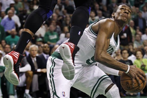 Boston Celtics point guard Rajon Rondo, right, pauses as he fakes Atlanta Hawks power forward Josh Smith to leap on a drive to the basket in the second quarter of Game 6 in a first-round NBA basketball playoff series in Boston, Thursday, May 10, 2012. (AP Photo/Charles Krupa)