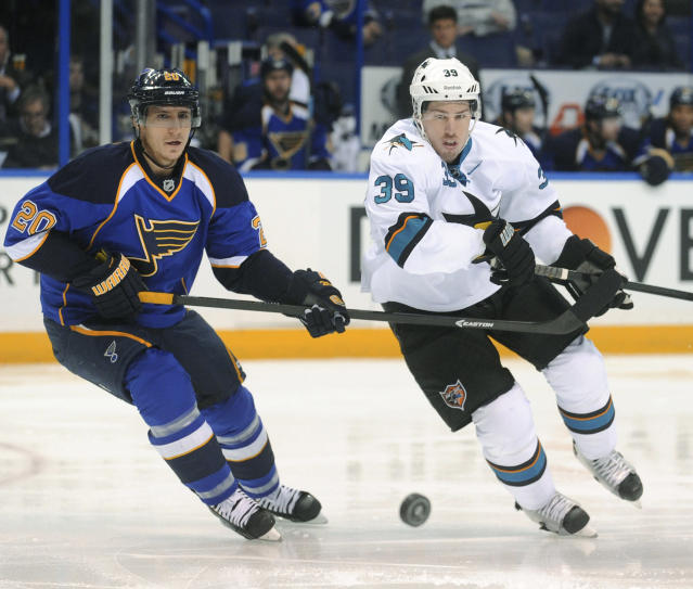 St. Louis Blues' Alexander Steen (20) and San Jose Sharks' Logan Couture (39) chase the puck during the first period of an NHL hockey game Tuesday, Oct. 15, 2013, in St. Louis. (AP Photo/Bill Boyce)