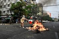 A protester throws items to a burning makeshift barricade during a protest against the military coup in Yangon