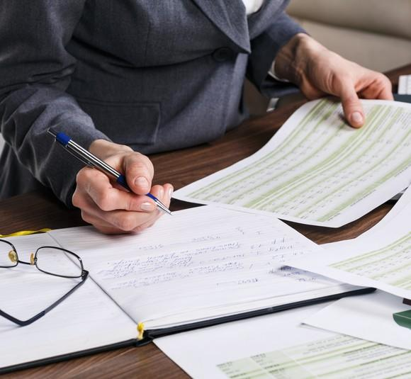 Close up of a female hand doing calculations on paper at an office desk.