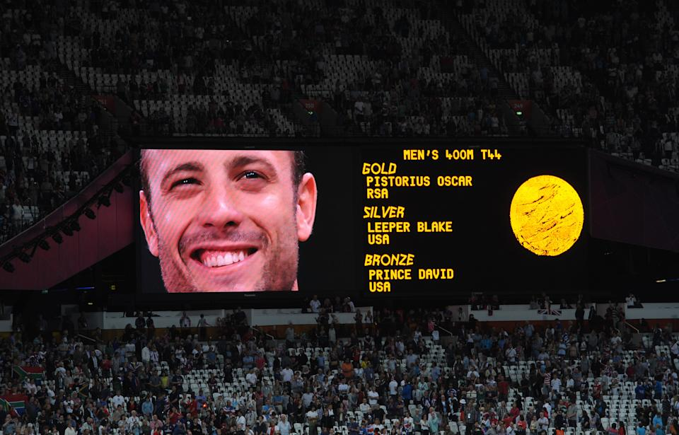 South Africa's Oscar Pistorius observes his national anthem on the big screen after receiving his Gold medal for the Men's 400m - T44 in the Olympic Stadium, Olympic Park, during the Paralympic Games in London.
