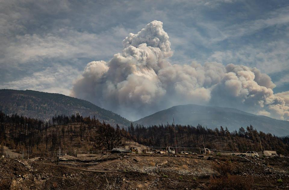 """<span class=""""caption"""">Properties destroyed by the Lytton Creek wildfire on June 30 are seen as a cloud produced by the fire rises in the mountains above Lytton, B.C. </span> <span class=""""attribution""""><span class=""""source"""">THE CANADIAN PRESS/Darryl Dyck </span></span>"""