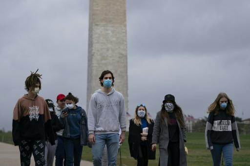 A group of young people wear protective masks as they walk near the Washington Monument on the National Mall