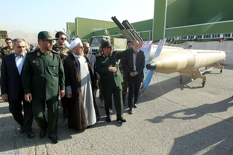 Iranian President Hassan Rouhani (centre) and Iran's Defence Minister Hossein Dehqan (2nd right) visit Iran's defence capabilities exhibition in Tehran on August 24, 2014