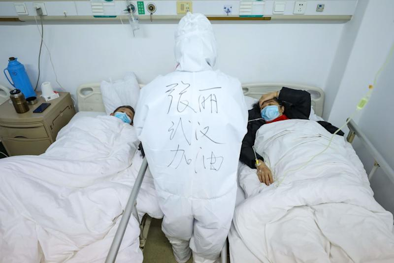 A doctor checks on two patients in a Wuhan hospital. Source: Getty