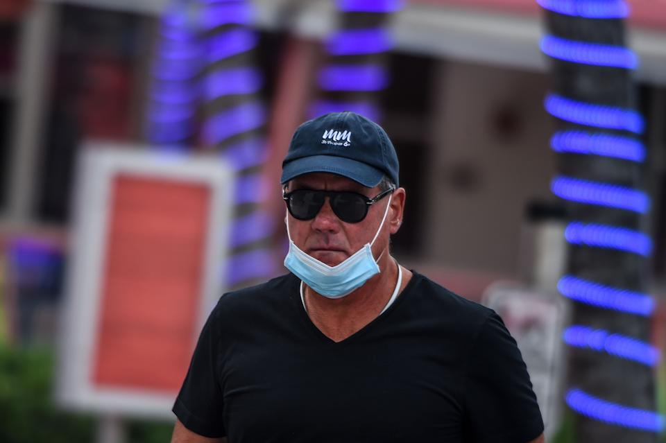 A man wears a facemask on his chin on Ocean Drive in South Beach, Miami, on May 19, 2020, amid the novel coronavirus pandemic. (Photo by CHANDAN KHANNA / AFP) (Photo by CHANDAN KHANNA/AFP via Getty Images)