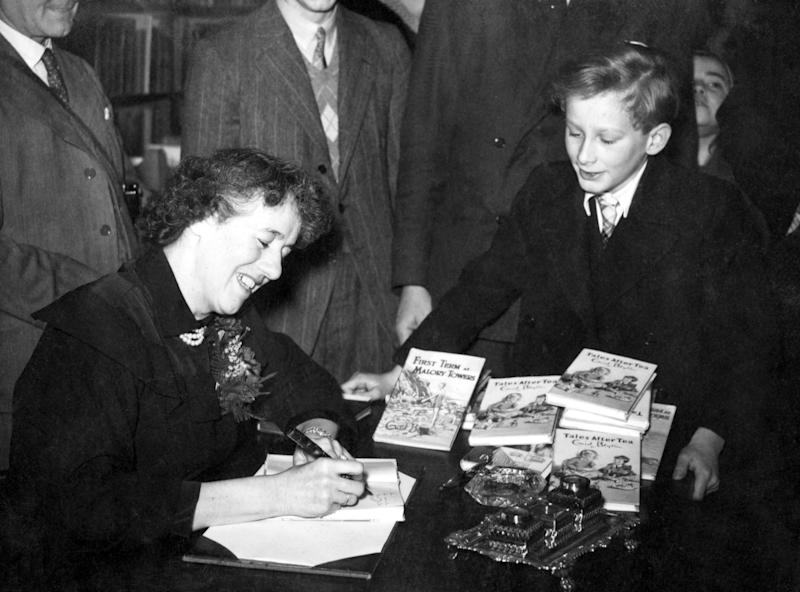 "Popular author of children's books, Enid Blyton in Hatchards, Piccadilly, London, where she gave a talk 'for children only', adults not being admitted. Afterwards she autographed copies of her books for her young audience. She obliges ""Oliver Twist"" (John Howard Davies who played the film part) with a signed copy of one of her books. (Photo by PA Images via Getty Images)"