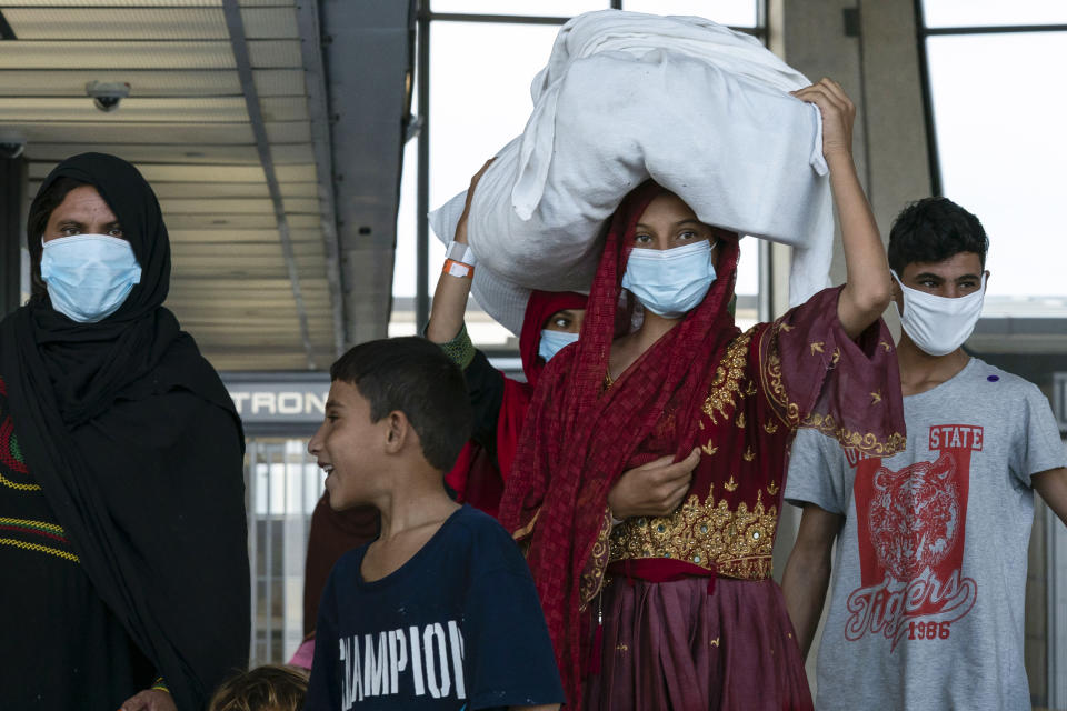 People evacuated from Kabul, Afghanistan, walk through the terminal before boarding a bus after they arrived at Washington Dulles International Airport, in Chantilly, Va., on Monday, Aug. 30, 2021. (AP Photo/Jose Luis Magana)