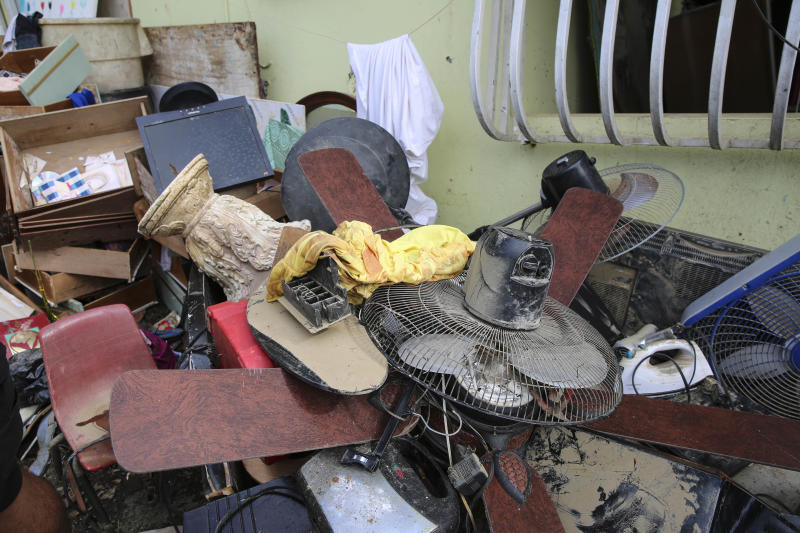 Juan Medina-Dishmey and his wife, Juana Ferrera, cleared out damaged belongings from their home in Valle Hill, Canóvanas, Puerto Rico. They told HuffPost they feared it may all be contaminated with the leptospirosis bacteria. (Carolina Moreno/HuffPost)