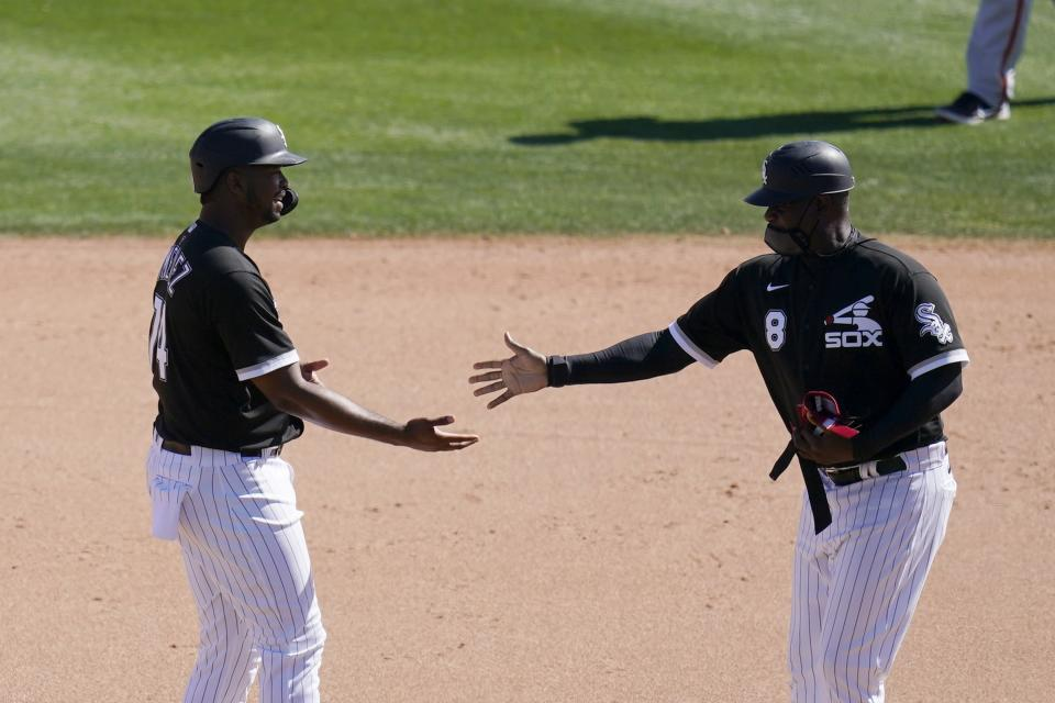 Chicago White Sox's Eloy Jimenez, left, is congratulated by first base coach Daryl Boston after Jimenez hit an RBI double against the San Francisco Giants during the fifth inning of a spring training baseball game Monday, March 22, 2021, in Phoenix. (AP Photo/Ross D. Franklin)