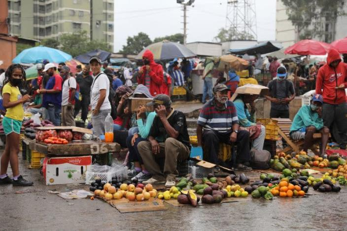 Sellers wait for customers under the rain at the Coche wholesale market amid coronavirus (COVID-19) disease outbreak in Caracas