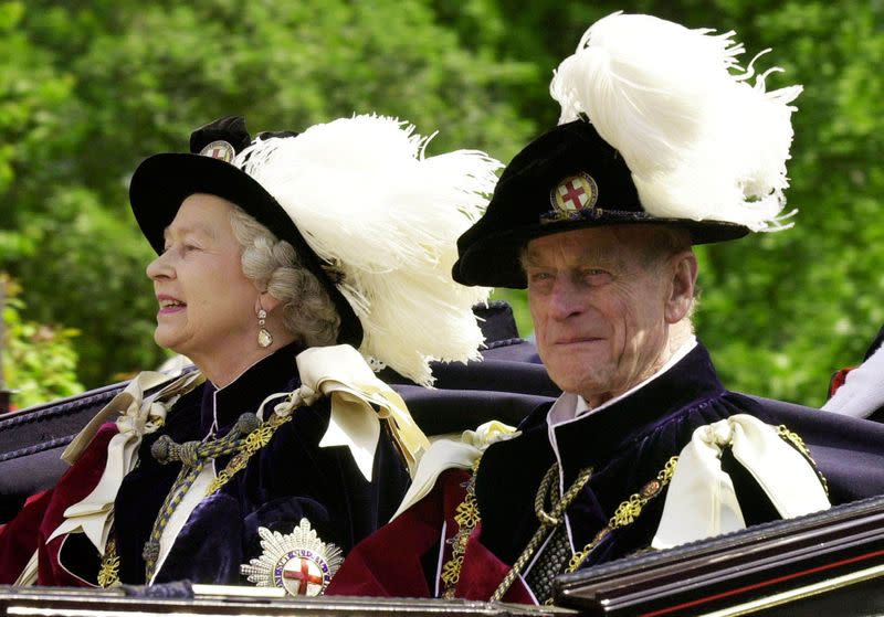 FILE PHOTO: Britain's Queen Elizabeth II and Prince Phillip, the Duke of Edinburgh, wearing their Order of the Garter robes, ride in an open-topped carriage to Windsor Castle