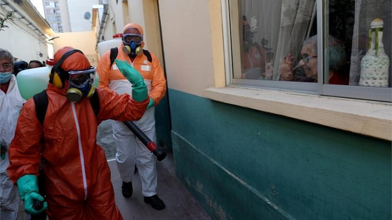 A worker wearing protective gear waves to a woman while using disinfectant to clean outside of a house in Santiago, Chile