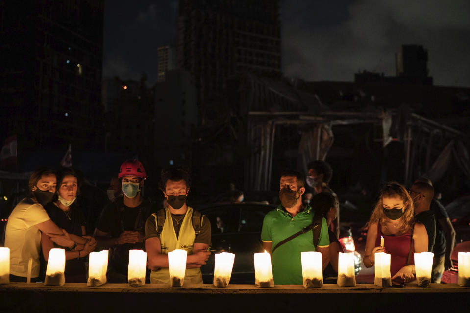 Demonstrators light candles honoring the victims of the deadly explosion at Beirut port which devastated large parts of the capital, in Beirut, Lebanon, Sunday, Aug. 9, 2020. (AP Photo/Felipe Dana)